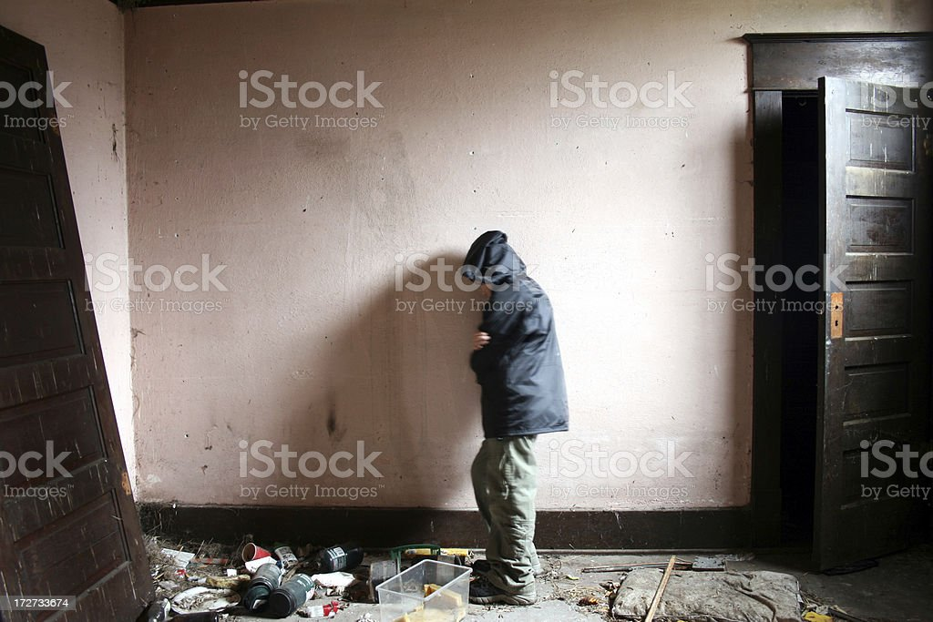 Boy huddled from cold in pink walled garbage strewn room royalty-free stock photo