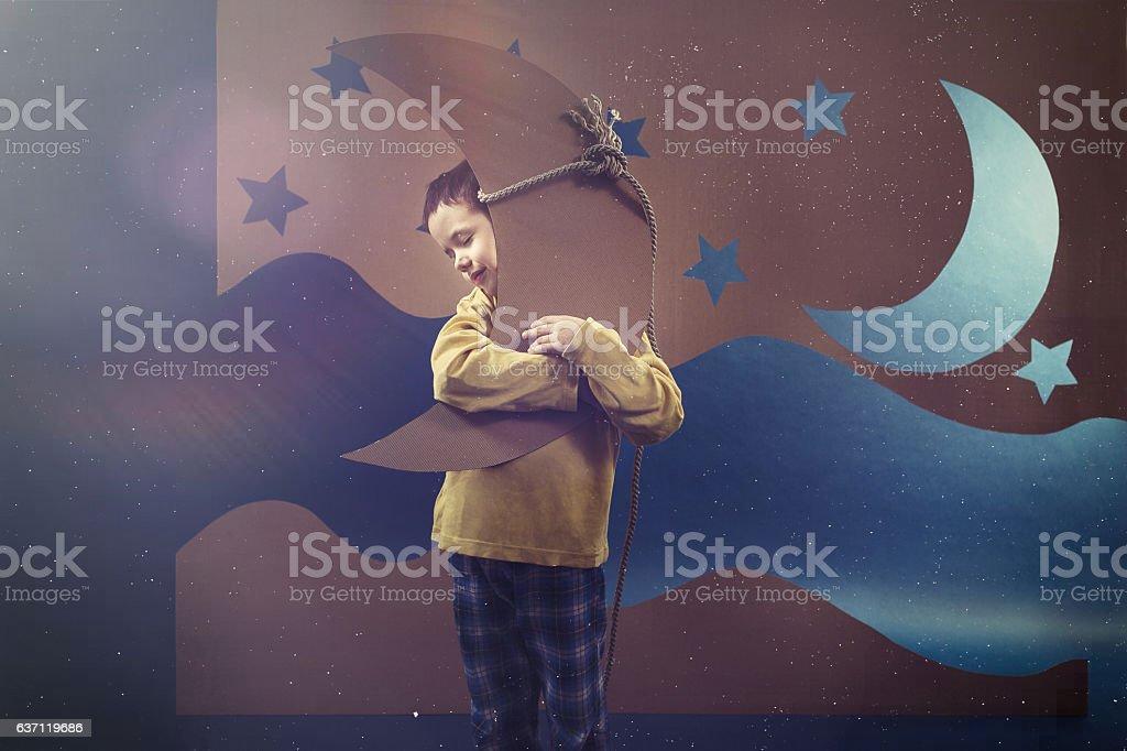 Boy hugging the moon stock photo