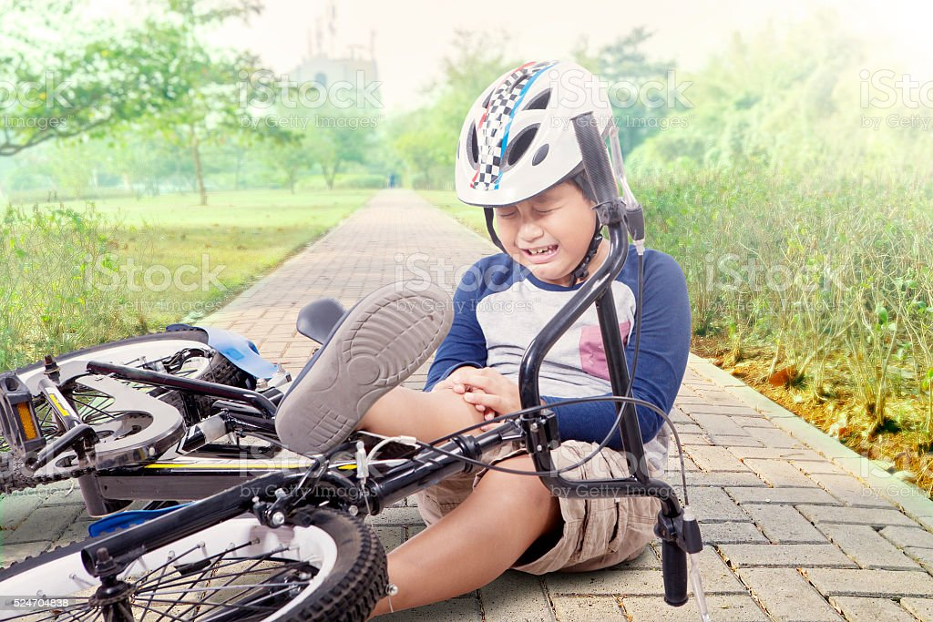 Boy hurt after falling off his bicycle stock photo