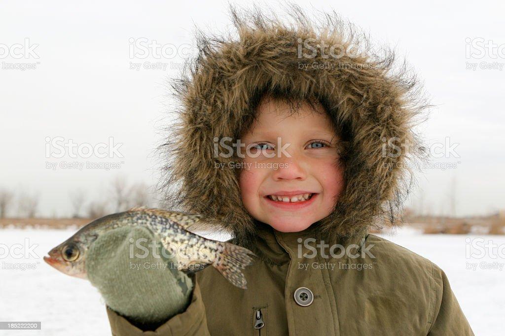 Boy Ice Fishing Holds Fish stock photo