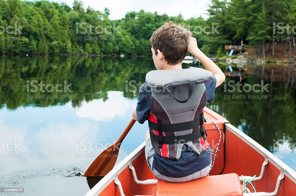boy in a canoe stock photo