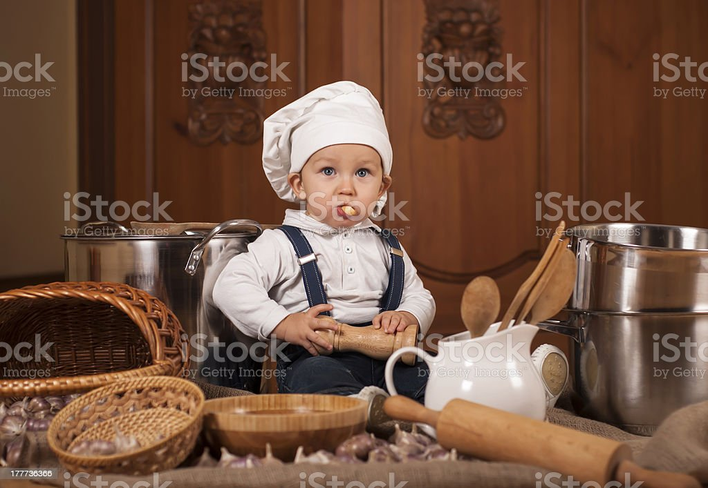 boy in a cook cap among pans and vegetables stock photo