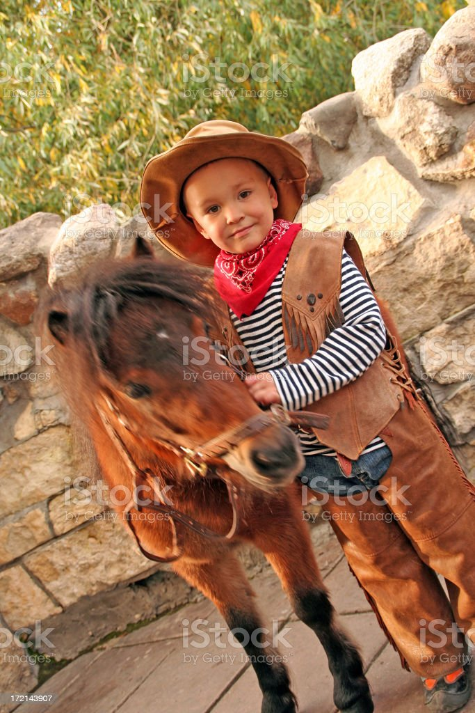 boy in a suit of the cowboy from  pony royalty-free stock photo