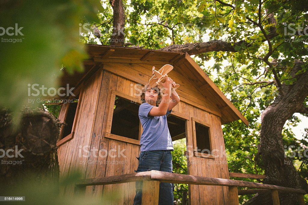 Boy in a treehouse daydreaming with his toy wooden plane stock photo