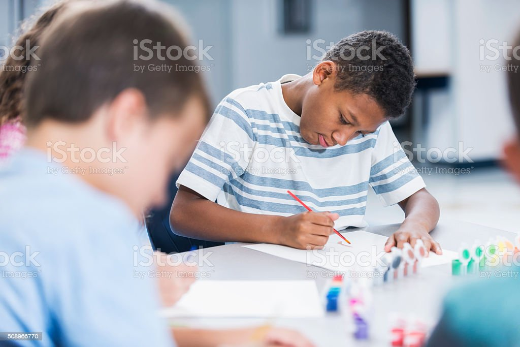 Boy in art class painting a picture stock photo