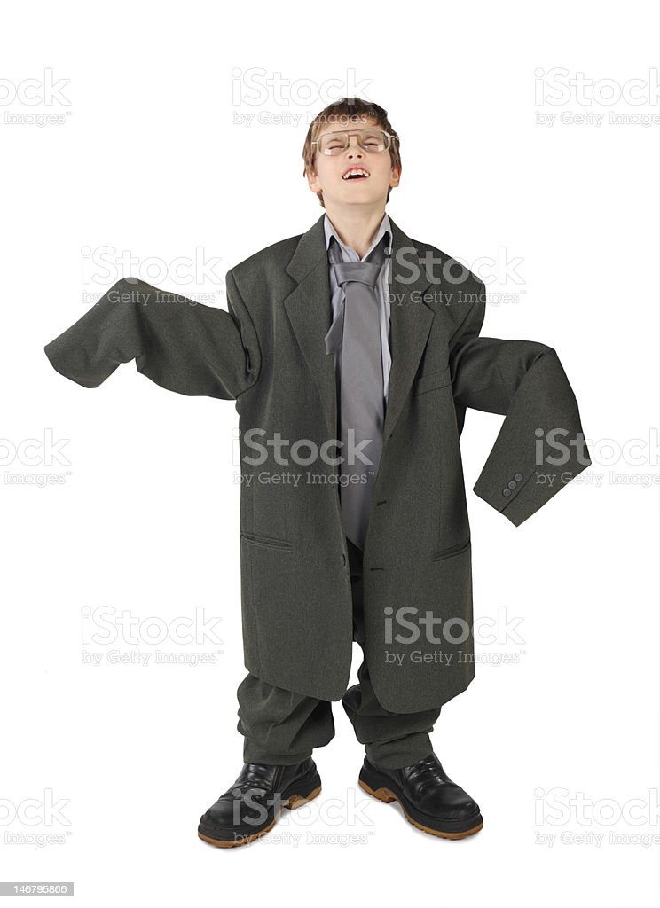 Boy in big grey man's suit, boots and glasses isolated stock photo