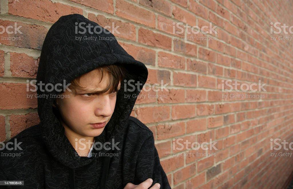 Boy in black hoodie leaning against brick wall royalty-free stock photo