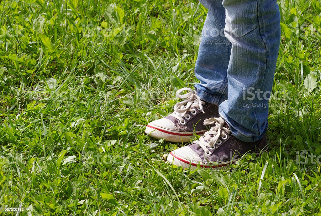 Boy in blue sneakers and jeans standing on the green stock photo