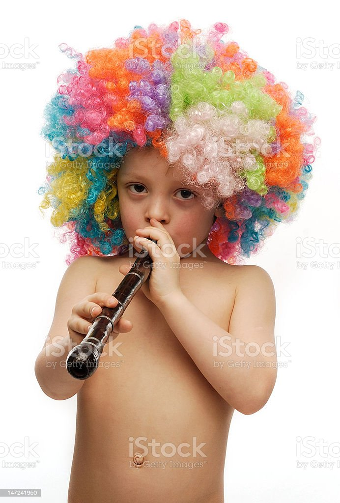Boy in colorful bright wig playing a pipe royalty-free stock photo