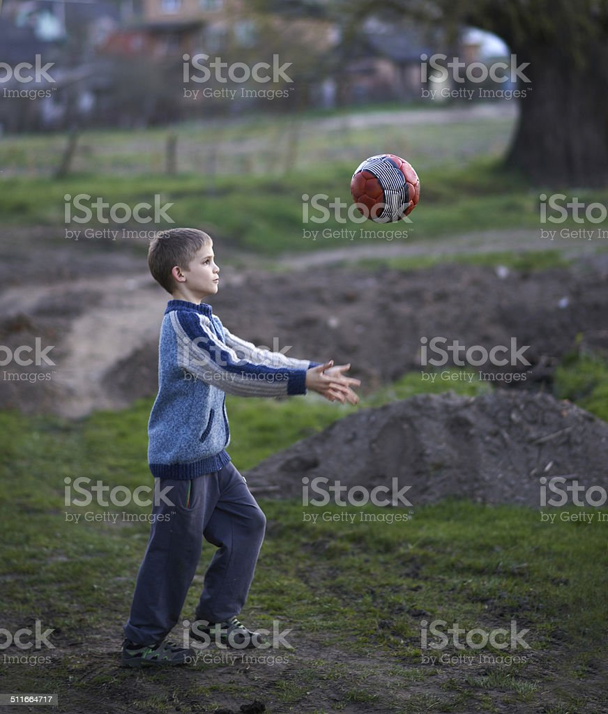 boy in countryside plays the ball stock photo