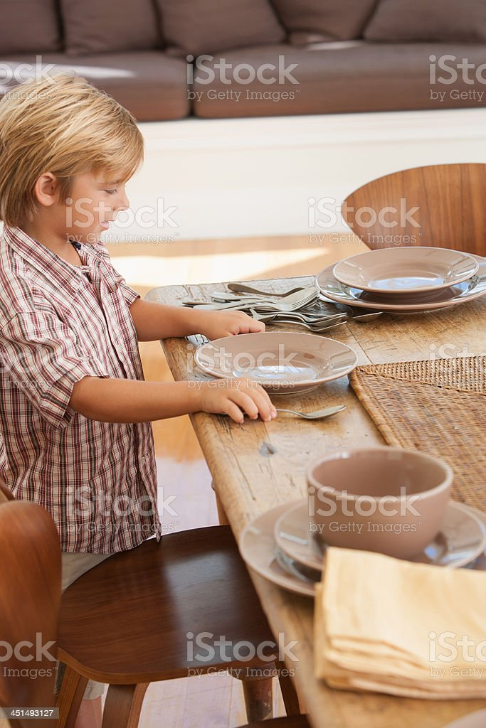 Boy in dining room setting table stock photo