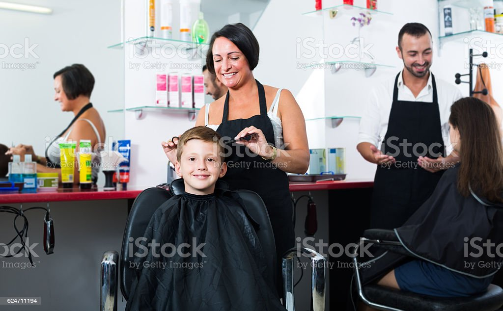 Boy in elementary school age getting hairdo by  hairdresser stock photo