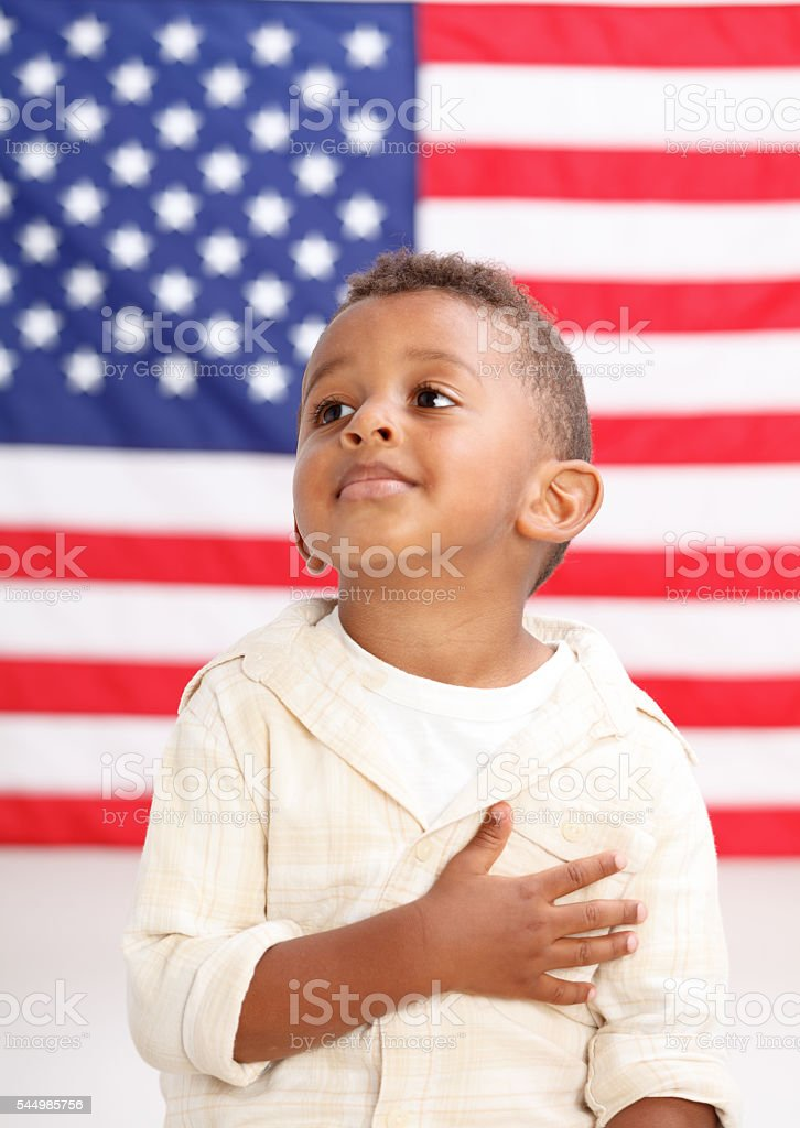 Boy in front of American flag with hand over heart stock photo