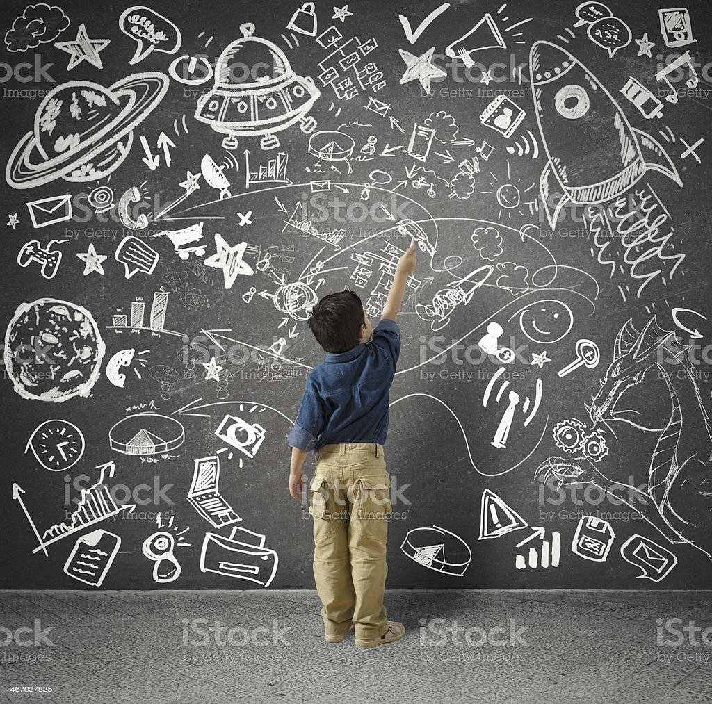 Boy in front of large chalkboard with images royalty-free stock photo
