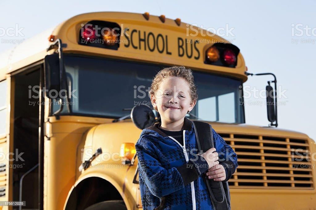 Boy in front of school bus stock photo