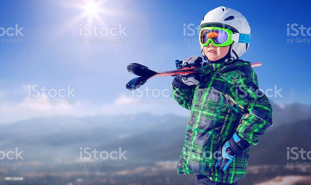 Boy in full ski equipment on the mountain view stock photo