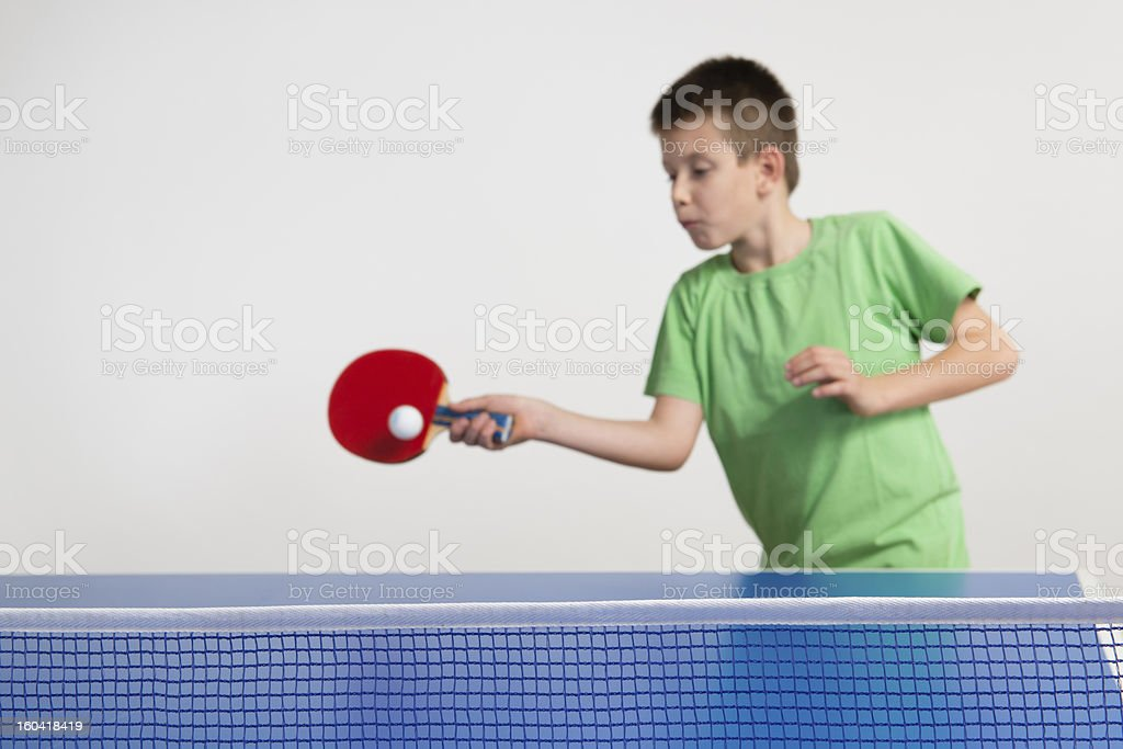 Boy in green shirt playing table tennis stock photo