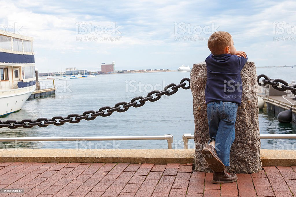 boy in harbor stock photo