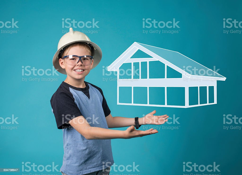 Boy in helmet with house in hands. Family home concept. stock photo