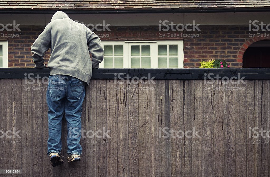 Boy in hoodie trespassing on private residential property stock photo