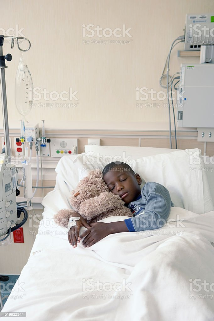 Boy in hospital bed stock photo