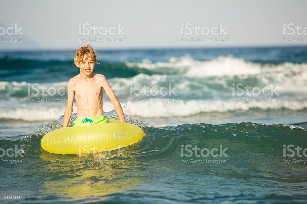 Boy in inflatable ring having fun, swimming stock photo