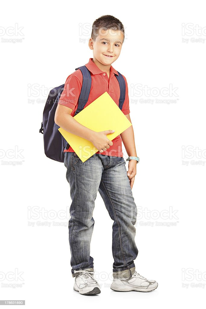 A boy in jeans holding a folder and carrying a backpack stock photo