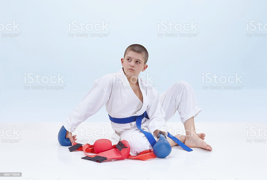 Boy in karategi sits near a karate outfit stock photo