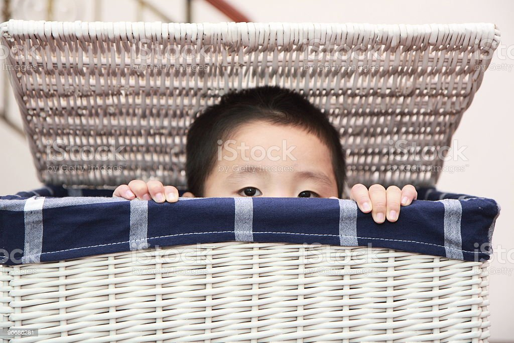 boy in laundry basket stock photo