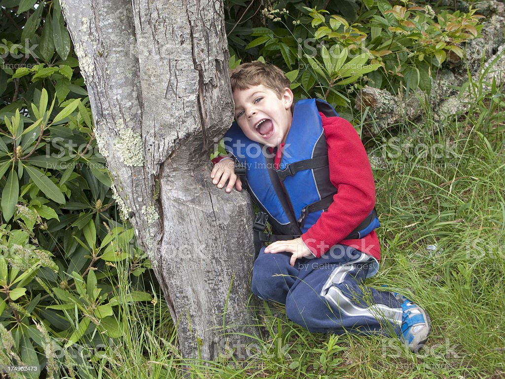 Boy In Life Vest Being A Beaver Eating Tree stock photo