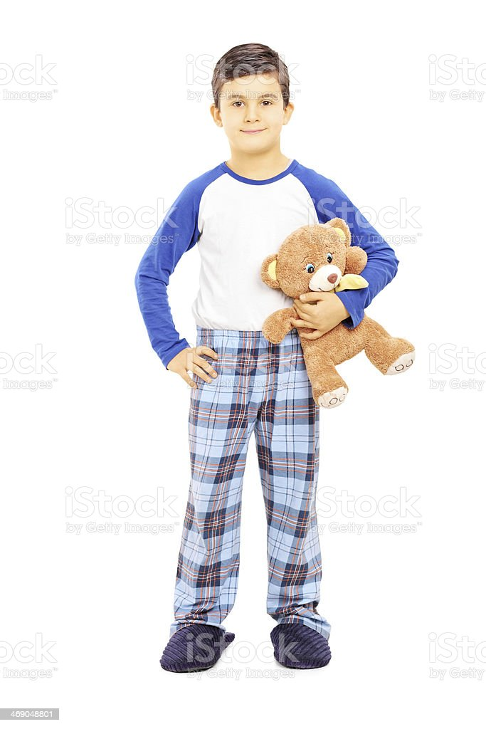 Boy in pajamas holding teddy bear stock photo