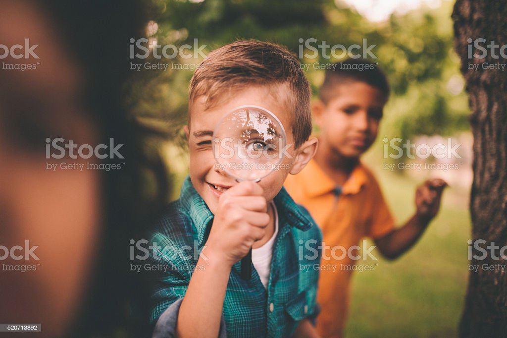 Boy in park holding a magnifying glass to his eye stock photo