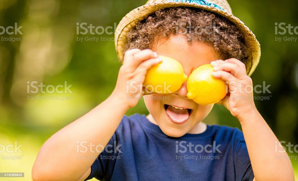 Boy in park holding lemons as eyes stock photo