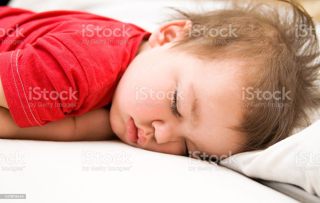 Boy in red dress sleeping on bed royalty-free stock photo