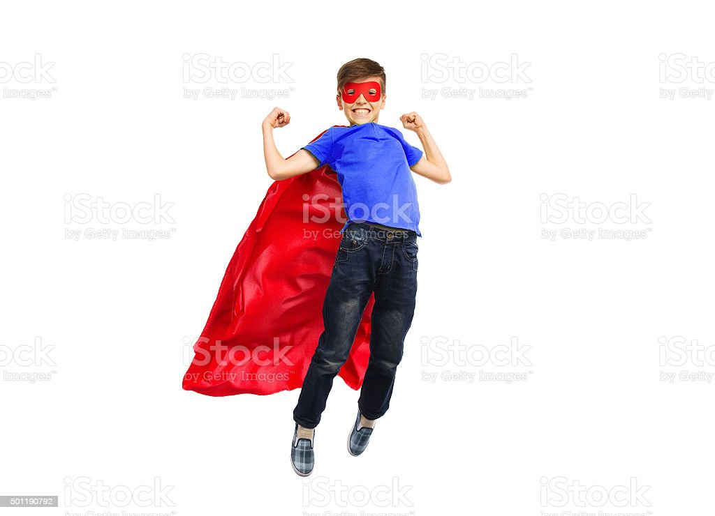 boy in red super hero cape and mask flying stock photo