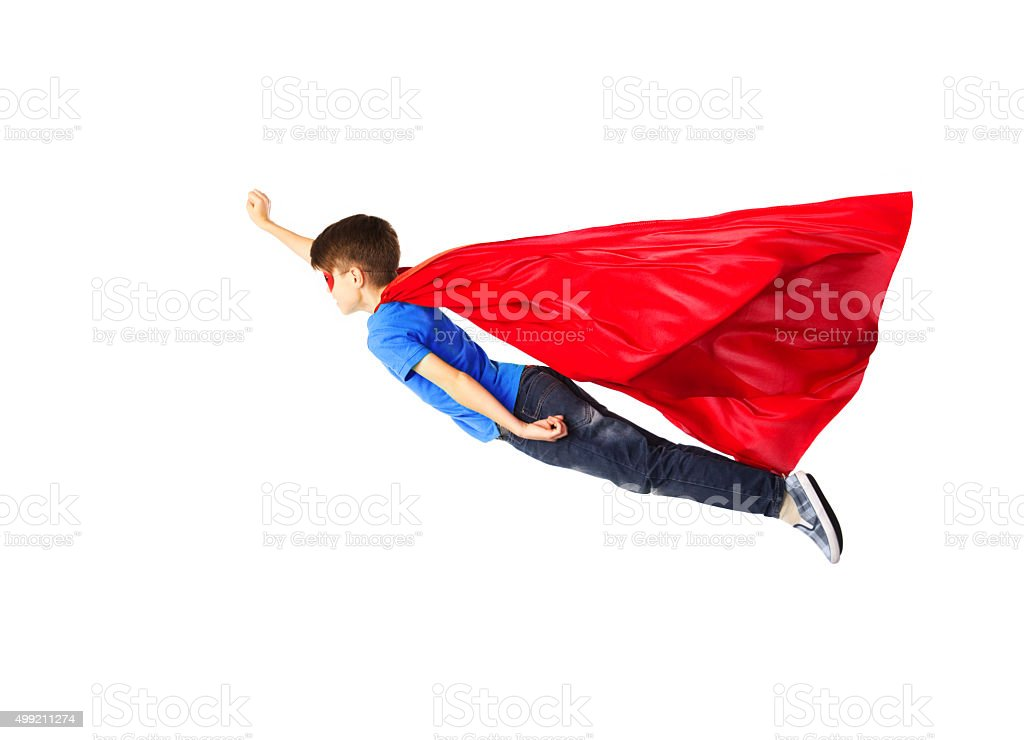 boy in red superhero cape and mask flying on air stock photo