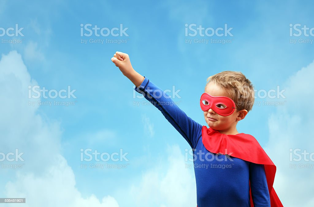 Boy in red superhero cape and mask stock photo