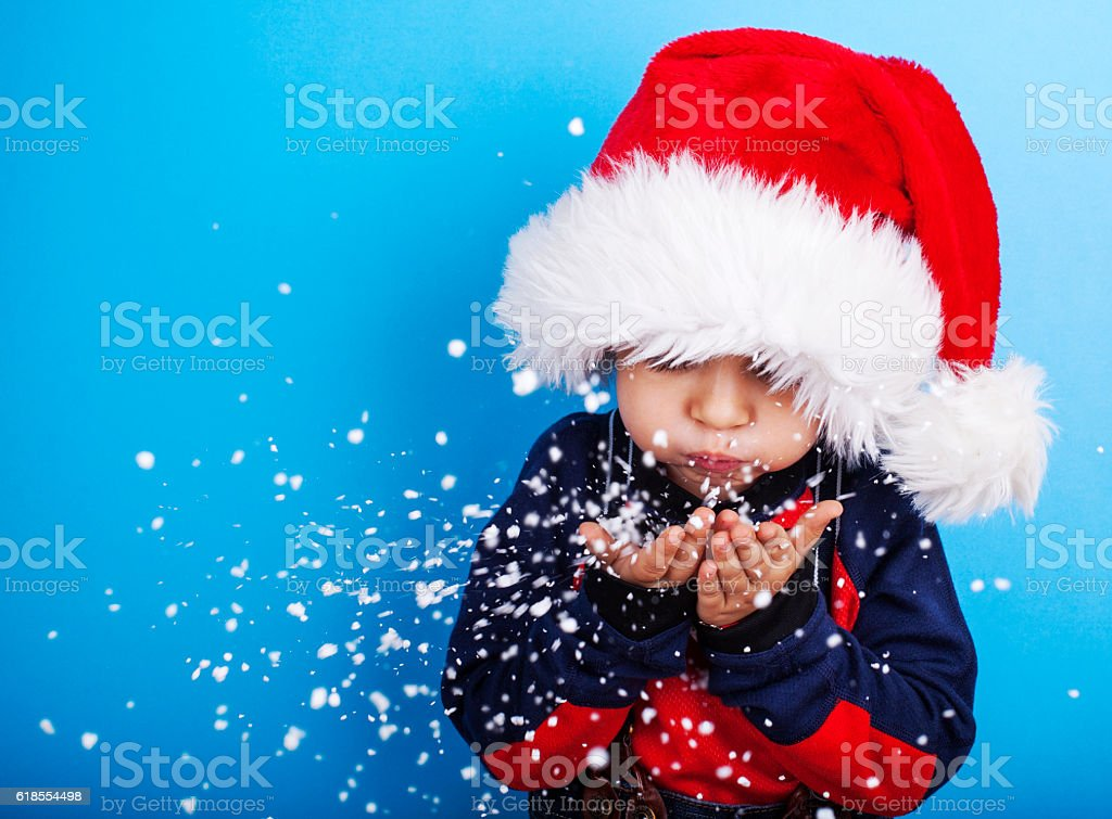 Boy in santa claus hat blowing snowflakes stock photo