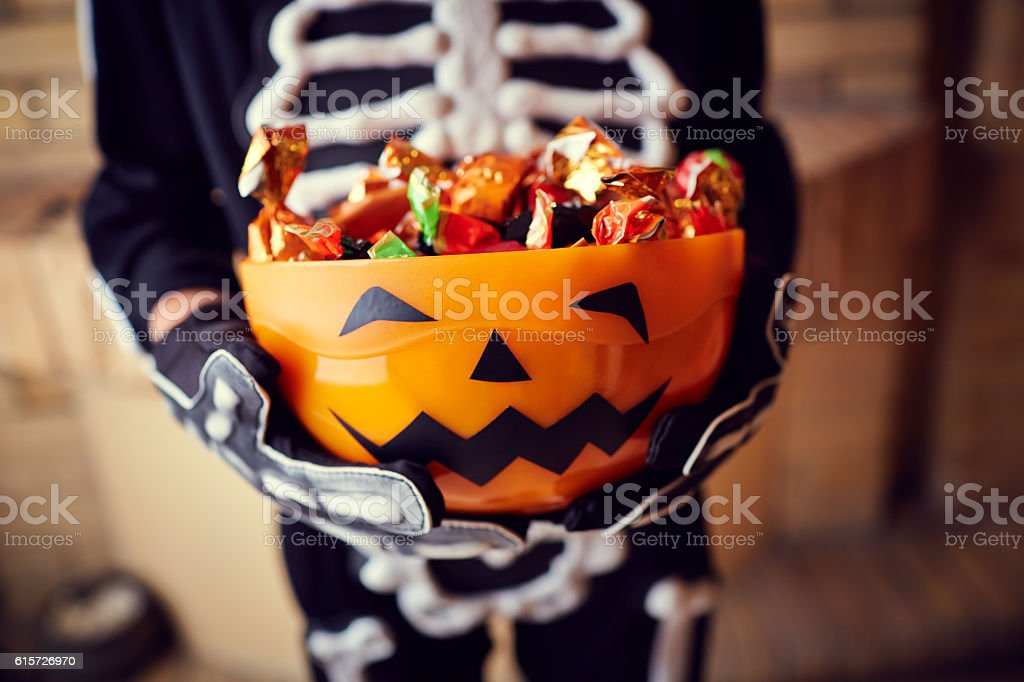 Boy in skeleton costume holding bowl full of candies stock photo