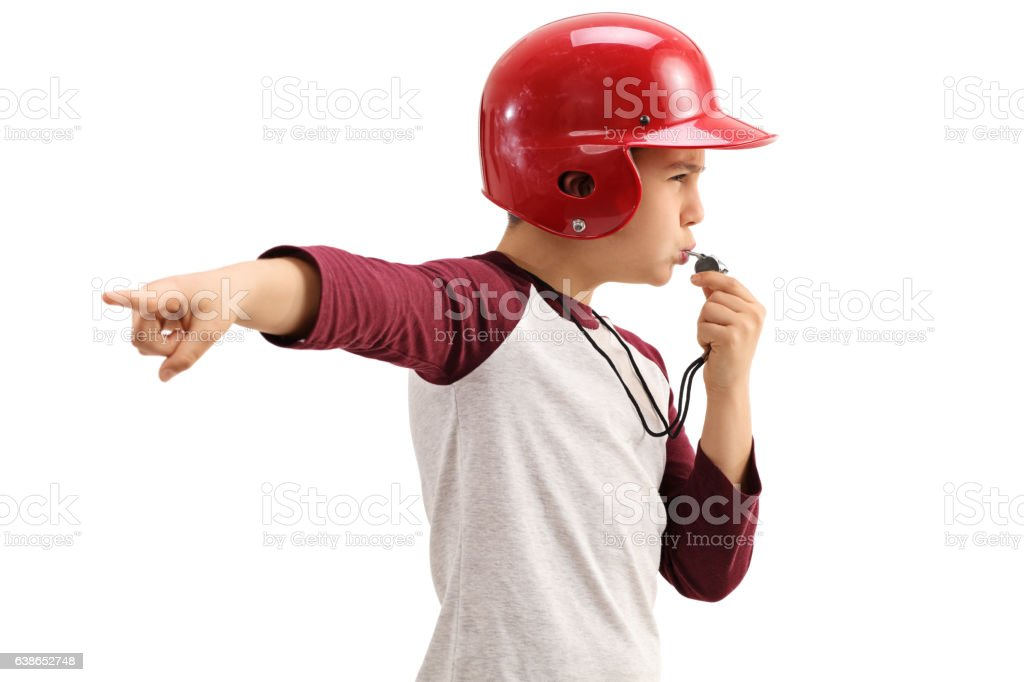 Boy in sportswear blowing whistle and pointing with his hand stock photo