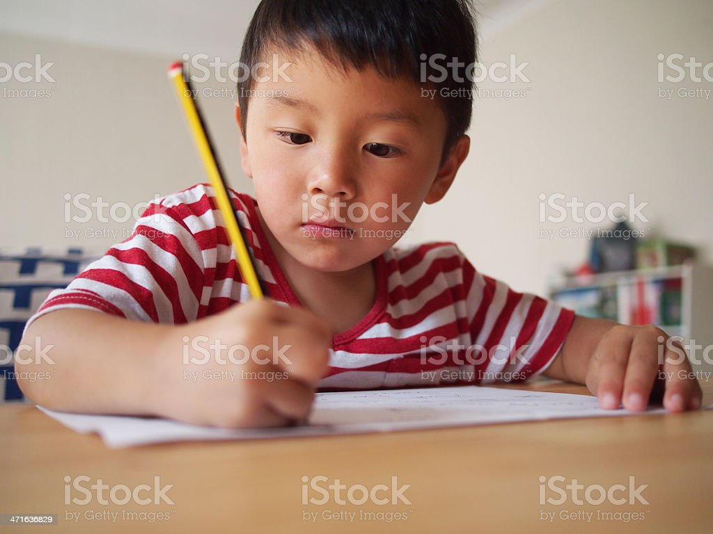 Boy in Striped Tshirt Writing royalty-free stock photo