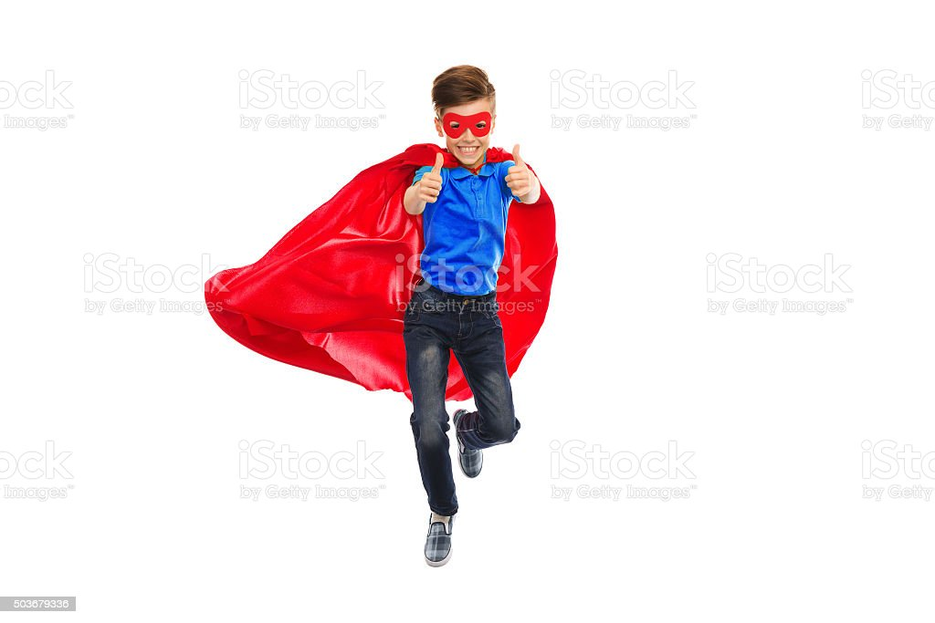 boy in super hero cape and mask showing thumbs up stock photo