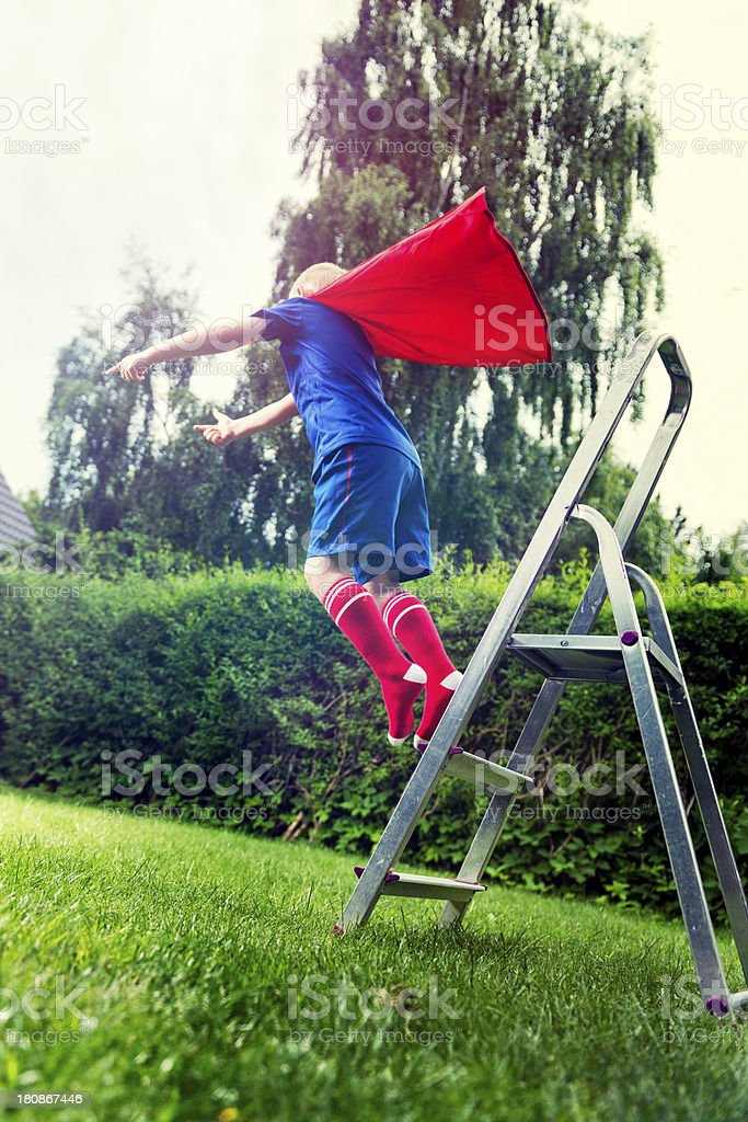 Boy in superhero outfit jumps from a ladder royalty-free stock photo