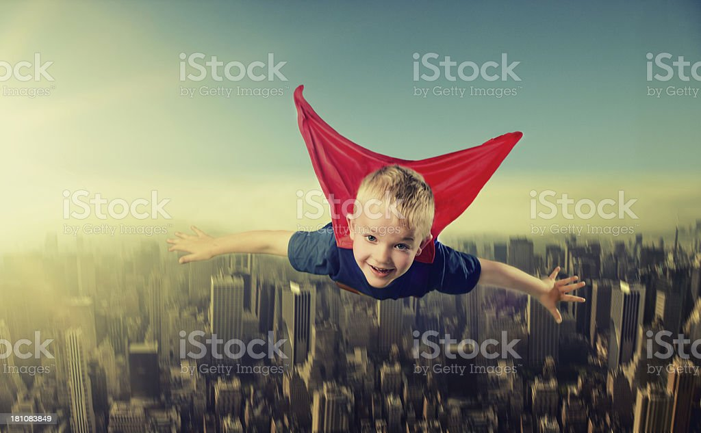 Boy in superman outfit flys over a big city royalty-free stock photo