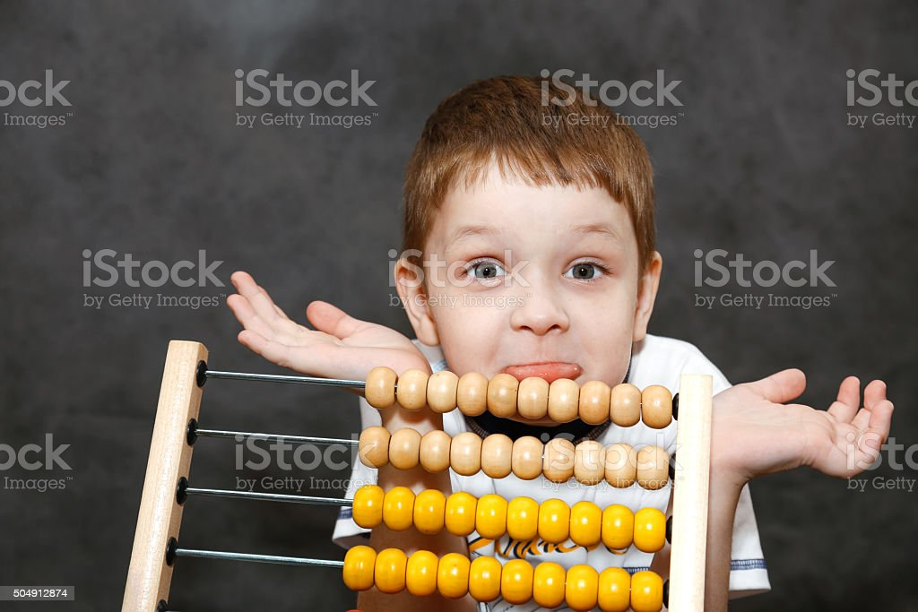 Boy in surprise spread his arms near the wooden abacus. stock photo
