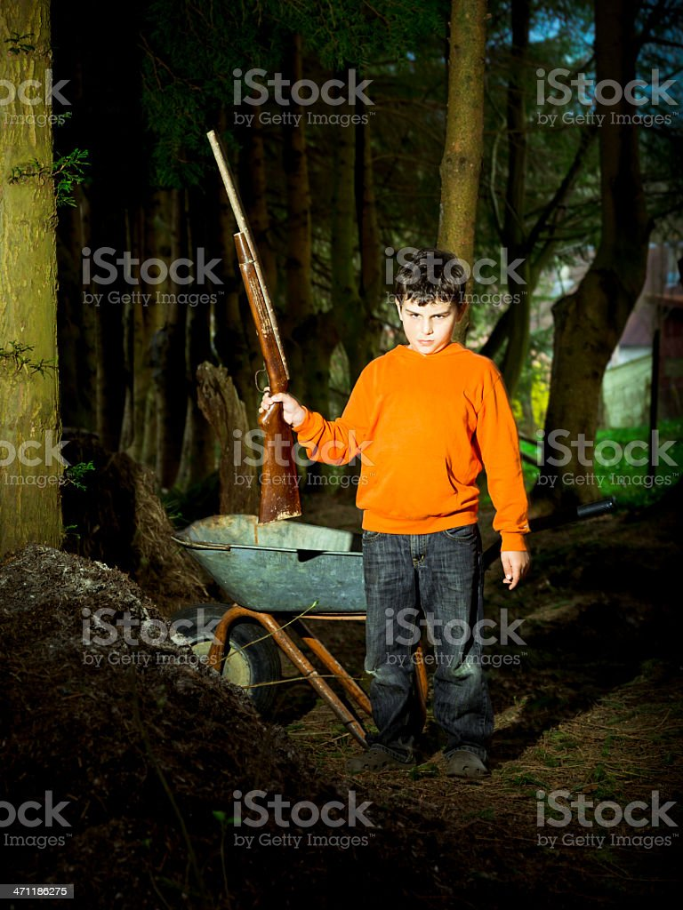 Boy in the forest with a wooden toy gun royalty-free stock photo
