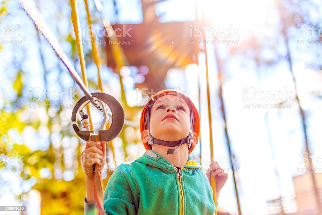 boy in the rope park looking up stock photo