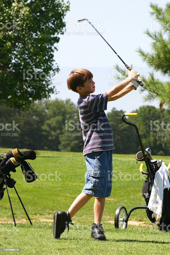 Boy in t-shirt and shorts swinging golf club on sunny day stock photo