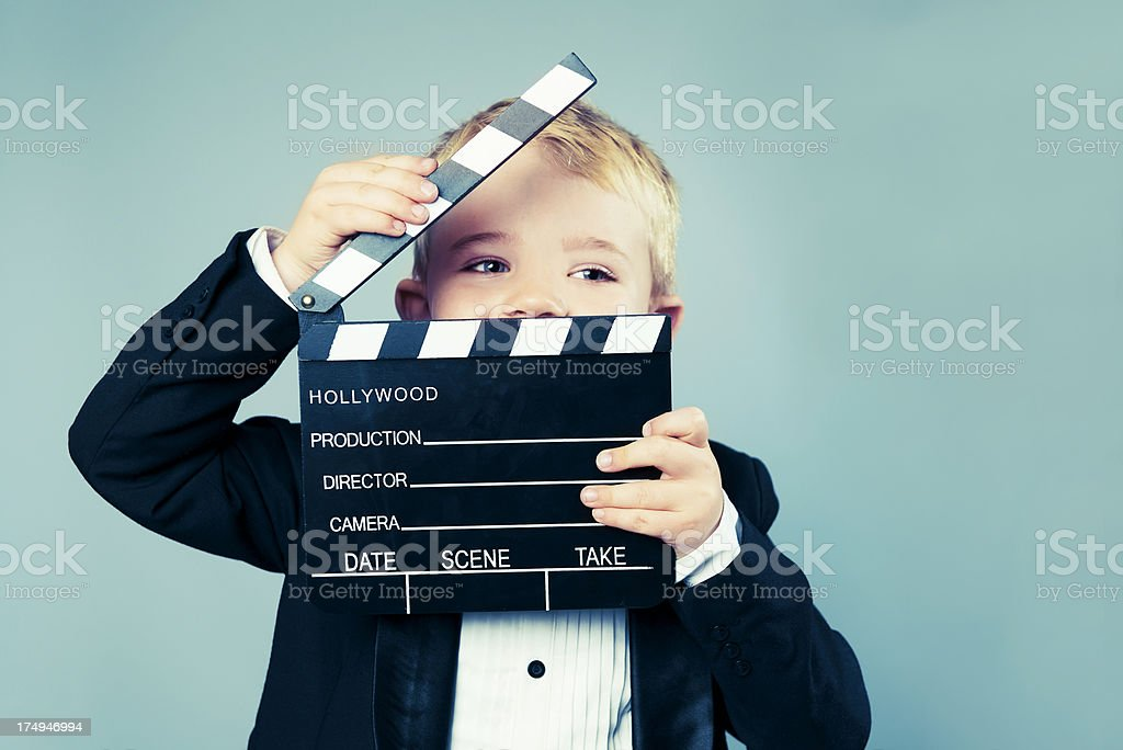 Boy in tuxedo holds a Hollywood slate board stock photo