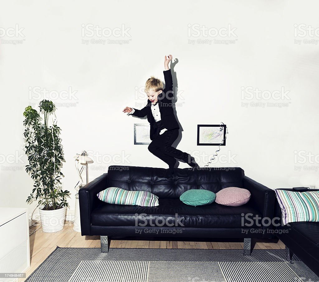 Boy in tuxedo jumps off sofa royalty-free stock photo
